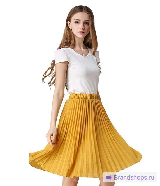 Девушка в желтой плиссированной юбке до колена