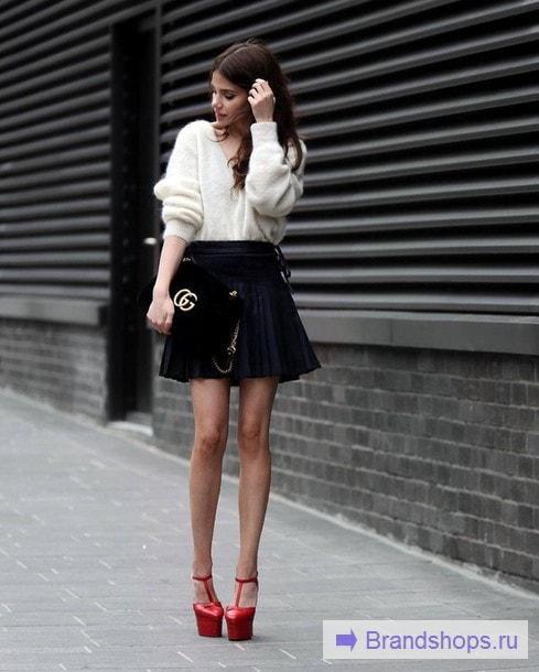 Девушка в короткой плиссировке и красных босоножках